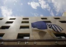 Una bandera de la Unión Europea (a la izquierda en la imagen) junto a una de Grecia en la puerta del banco central en Atenas, jun 11 2015. El Gobierno de Grecia está dispuesto a alcanzar un acuerdo con sus acreedores pronto y quiere intensificar las negociaciones sobre temas pendientes como el presupuesto y la reestructuración de la deuda, dijo el jueves un portavoz luego de que el FMI aseguró que su equipo había dejado las discusiones en Bruselas. REUTERS/Yannis Behrakis