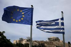 A European Union flag (L) and a Greek national flag flutter as the ancient Parthenon temple is seen in the background in Athens June 1, 2015. REUTERS/Alkis Konstantinidis