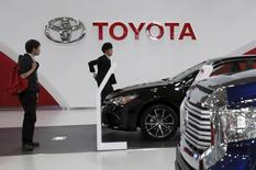 People walk under a logo of Toyota Motor Corp at the company's showroom in Tokyo, Japan, May 8, 2015.  REUTERS/Yuya Shino