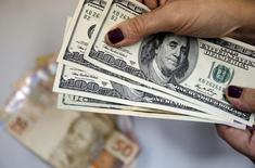 Mulher com notas de dólares e de real 31/3/2015 REUTERS/Sergio Moraes