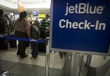 People wait in line at the JetBlue counter at La Guardia airport in New York January 6, 2014. REUTERS/Carlo Allegri