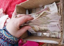 Продавщица мяса на красноярском рынке кладет деньги в коробку. 14 января 2015 года. Российский Минфин хочет контролировать долговую нагрузку регионов, поделив их на группы по степени риска, и оказывать им помощь по схеме поддержки МВФ европейских стран. REUTERS/Ilya Naymushin