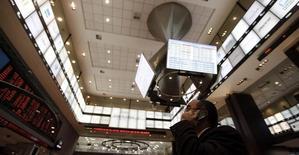 Un hombre habla por celular mientras mira un tablero electrónico que muestra el índice Bovespa de la Bolsa de Sao Paulo, en Brasil, 4 de agosto de 2011. El principal índice de acciones de Brasil subía el martes y se encaminaba a dejar atrás tres sesiones de pérdidas, en medio de un mejor ambiente externo y con los papeles de los bancos entre los principales impulsores del avance. REUTERS/Nacho Doce