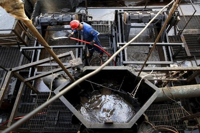 The flow of crude oil is seen in a container while an oilfield worker works on a drilling rig at an oil well operated by Venezuela's state oil company PDVSA, in the oil rich Orinoco belt, near Cabrutica at the state of Anzoategui April 16, 2015.  REUTERS/Carlos Garcia Rawlins