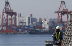 A worker walks near a container area at a port in Tokyo, February 19, 2015. REUTERS/Toru Hanai