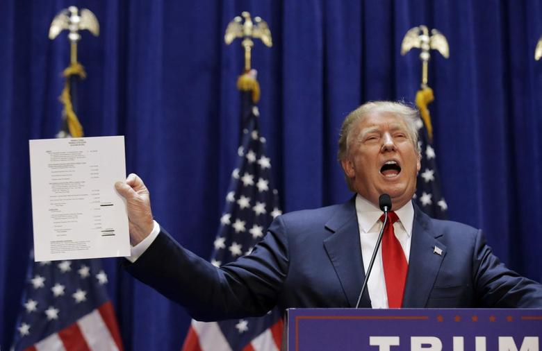 Republican presidential candidate, real estate mogul and TV personality Donald Trump holds up his financial statement showing his net worth as he formally announces his campaign for the 2016 Republican presidential nomination during an event at Trump Tower in New York, June 16, 2015. REUTERS/Brendan McDermid