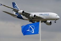 Un Airbus A380 au-dessus d'un fanion Boeing lors d'un vol au Salon du Bourget. Airbus a remporté plus de commandes que Boeing au Salon du Bourget cette semaine, grâce à un contrat de dernière minute avec la compagnie à bas coûts Wizz Air, qui s'ajoute à une demande toujours soutenue des compagnies asiatiques./Photo prise le 18 juin 2015/REUTERS/Pascal Rossignol