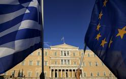 Protesters hold an EU flag and a Greek flag (L) as people gather at the entrance of the Greek parliament, during a rally calling on the government to clinch a deal with its international creditors and secure Greece's future in the Eurozone, in Athens June 18, 2015.   REUTERS/Yannis Behrakis
