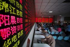 Inversores miran las pantallas de computador que muestran la información de las acciones, en una agencia de la bolsa en Shanghái, 26 de mayo de 2015. Las acciones en China cayeron el viernes, cerrando su peor semana desde la crisis financiera global luego de que un repunte de ocho meses en el país pareció quedar sin combustible. REUTERS/Aly Song