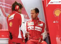 Ferrari Formula One driver Sebastian Vettel of Germany (R) talks to a technician in the pit during the first practice session of the Austrian F1 Grand Prix at the Red Bull Ring circuit in Spielberg, Austria, June 19, 2015.  REUTERS/Leonhard Foeger