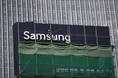 A worker works on a Samsung outdoor advertisement installed atop an office building in central Seoul March 23, 2015. REUTERS/Kim Hong-Ji