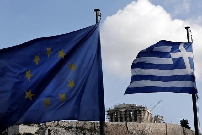 6月21日、ギリシャは、支援の期限が月末に迫るなか今週の債権団との協議で合意できなければ、2013年に資本規制に追い込まれたキプロスのような道をたどる可能性がある。写真は、EUの旗とギリシャ国旗、1月撮影(2015年 ロイター/Alkis Konstantinidis)