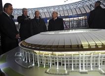 El ministro de Deporte ruso, Vitaly Mutko (izqda.), el presidente Vladimir Putin (centro), y Joseph Blatter (segundo a la derecha), escuchan al alcalde de Moscú, Sergei Sobyanin, en el estadio Luzhniki, el que está en construcción, en Moscú, 28 de octubre de 2014. El Gobierno ruso ordenó el lunes recortes por 30.000 millones de rublos (560 millones de dólares) en los gastos previstos para el Mundial de fútbol del 2018, pero dijo que la construcción de estadios no sería afectada. REUTERS/Mikhail Klimentyev/RIA Novosti/Kremlin   ESTA IMAGEN HA SIDO PROVISTA POR UNA TERCERA PARTE. ES DISTRIBUIDA, EXACTAMENTE COMO FUE RECIBIDA POR REUTERS, COMO UN SERVICIO A LOS CLIENTES SOLO PARA USO EDITORIAL. NO DISPONIBLE PARA CAMPAÑAS DE MARKETING O PUBLICIDAD.