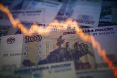 """График колебания пары рубль/доллар на фоне рублевых купюр в Варшаве 7 ноября 2014 года. Банк России считает """"нереалистичным"""" повторение декабрьской волатильности курса рубля и рассчитывает на экспортеров, которые обеспечат стабильный приток валюты на рынок. REUTERS/Kacper Pempel"""