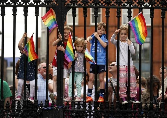 Children wave rainbow flags as they stand with their same-sex marriage supporting parents at Dublin Castle in Dublin, Ireland May 23, 2015.  REUTERS/Cathal McNaughton