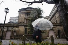 Человек проходит мимо здания Банка Японии в Токио 18 февраля 2015 года. Некоторые члены совета Банка Японии выразили обеспокоенность слабым ростом потребительских цен в Токио и заявили, что за ситуацией необходимо наблюдать, чтобы понять, какие последствия эта слабость может оказать на потребительские цены всей страны. REUTERS/Thomas Peter