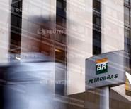 Una persona camina delante del logo de Petrobras, frente a la sede de la compañía en Sao Paulo, 23 de abril de 2015. La mayor investigación por corrupción en la historia de Brasil durará al menos dos años más y podría ampliarse involucrando a más de una decena de empresas extranjeras y a la eléctrica local Eletrobras, informó el martes un fiscal. REUTERS/Paulo Whitaker