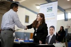Una mujer le da la mano a un hombre que busca trabajo, en una feria de empleos en Burbank, Los Angeles, California, 19 de marzo de 2015. El número de estadounidenses que presentaron nuevas solicitudes de subsidios por desempleo subió modestamente la semana pasada, pero las condiciones del mercado laboral siguieron mejorando. REUTERS/Lucy Nicholson