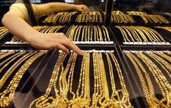Un empleado ordena joyas de oro en el mostrador, en una tienda de oro en Wuhan, provincia de Hubei, 25 de agosto de 2011. China planea lanzar un sistema de fijación del precio del oro denominado en yuanes a finales de año a través de la Bolsa de Oro de Shanghái (SGE, por su sigla en inglés), en una medida que apunta a dar al mayor productor y principal consumidor del lingote más influencia sobre los precios. REUTERS/Stringer