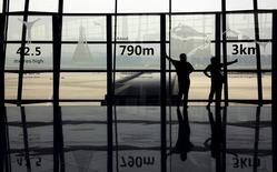 Two people watch planes land as they stand in the terminal three building of the Beijing Capital International Airport in this July 11, 2011 file photo.   REUTERS/David Gray/Files