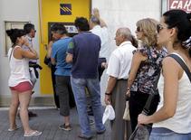Griegos hacen fila frente a los cajeros automáticos en una filial del Banco Piraeus en la isla de Creta.  Los bancos y la bolsa de Grecia permanecerán cerrados el lunes después de que los acreedores se rehusaron a extender el rescate del país, mientras los ahorradores hacían fila para retirar dinero, llevando el enfrentamiento de Atenas con la Unión Europea y el Fondo Monetario Internacional a un nuevo nivel. REUTERS/Stefanos Rapanis