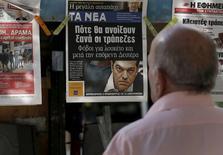 Los griegos se enfrentaban el lunes a un festivo bancario, a cajeros automáticos que no funcionaban y a un clima de rumores y teorías conspirativas después de que un colapso de las negociaciones entre Atenas y sus acreedores sumiera al país en una crisis profunda. En la imagen, un hombre lee titulares en un quiosco de Atenas el 29 de junio de 2015.  REUTERS/Yannis Behrakis