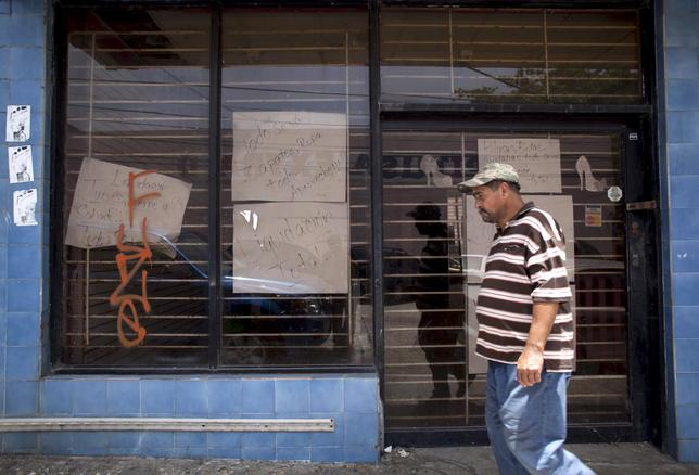 A man walks past a closed store with signs reading ''Closing down sale'' and ''Everything goes, shoes, clothes, take advantage'' in Arecibo, Puerto Rico, June 29, 2015. REUTERS/Alvin Baez-Hernandez