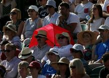 A couple shelter from the sun with a red umbrella at the Wimbledon Tennis Championships in London, June 29, 2015.   REUTERS/Stefan Wermuth
