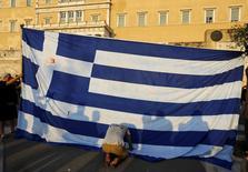 Un manifestante se arrodilla frente a la bandera de Grecia, durante una protesta anti-austeridad, en Atenas, Grecia, 29 de junio de 2015. Grecia entregó a sus acreedores un nueva propuesta de ayuda a dos años pidiendo una reestructuración paralela de la deuda, dijo la oficina del primer ministro Alexis Tsipras el martes, en lo que pareció un esfuerzo de último minuto por parte de Atenas para resolver un estancamiento con sus prestamistas. REUTERS/Yannis Behrakis