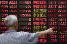 Un inversor observa un panel con información financiera en una correduría en Shanghái, jun 30 2015. Pese a las palabras tranquilizadoras de los reguladores de que la deuda marginal para comprar acciones en las bolsas chinas es manejable, el apalancamiento total podría llegar hasta 645.000 millones de dólares, lo que amplifica el riesgo no sólo para los inversores minoristas sino también para el sector empresarial. REUTERS/Aly Song