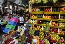 Un hombre compra frutas mientras otro transporta cajas, en un mercado en el distrito de Miraflores en Lima, 4 de marzo de 2014. Perú registró una inflación de 0,33 por ciento en junio, muy por encima de lo esperado por analistas, impulsada por un alza en los precios de los combustibles tras un desabastecimiento de gas, que también incidió en un aumento de las tarifas de transportes, dijo el miércoles el Gobierno. REUTERS/Mariana Bazo