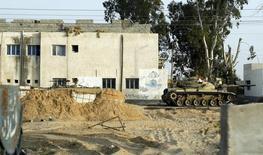 """Танк у школы между городами Эль-Ариш и Шейх Зувайед в провинции Северный Синай, Египет 25 мая 2015 года. По меньшей мере 50 человек погибли в результате скоординированного нападения боевиков """"Исламского государства"""" на ряд армейских блокпостов в египетском Северном Синае, ставшего самым кровопролитным в череде подобных инцидентов в провинции, сообщили источники в службах безопасности страны. REUTERS/Asmaa Waguih"""