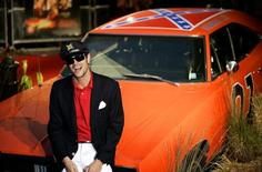 "Actor Johnny Knoxville of the U.S. sits on the ""General Lee"" car at the film premiere of ""The Dukes of Hazzard"" at the Vue Cinema, Leicester Square, London August 22, 2005. REUTERS/Dylan Martinez"