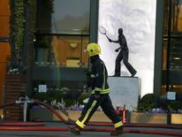 A fireman walks past the statue of Fred Perry after a fire inside Centre Court in Wimbledon at the end of play during the Tennis Championship, in London, 1 July, 2015. REUTERS/Henry Browne