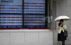 Una mujer mira su celular junto a un tablero que muestra los índices de mercado afuera de una agencia de la bolsa en Tokio, 30 de junio de 2015. Las bolsas de Asia subían el jueves por tercer día consecutivo a pesar de que la inquietud sobre un declive de las acciones chinas y el enfrentamiento de Grecia con sus acreedores limitaban las ganancias, mientras que el dólar se vio reforzado por unos datos económicos optimistas en Estados Unidos. REUTERS/Toru Hanai