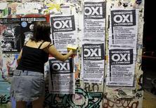 """Женщина клеит на стену постеры о грядущем референдуме со словом """"нет"""" на греческом в  Афинах 1 июля 2015 года. Для Греции, вероятно, """"не будет места в еврозоне"""", если она проголосует """"против"""" на воскресном референдуме о том, соглашаться ли на условия дальнейшей финансовой помощи, предупредил председатель Еврогруппы в четверг. REUTERS/Jean-Paul Pelissier"""