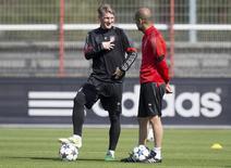 Técnico do Bayern de Munique, Pep Guardiola (direita), conversa com o meia Bastian Schweinsteiger durante treino do time no centro de treinamento do clube, em Munique. 20/04/2015 REUTERS/Lukas Barth