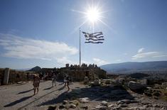 Una bandera de Grecia flameando sobre la Acrópolis en Atenas, jul 2 2015. El Fondo Monetario Internacional advirtió el jueves de que Grecia necesitaría una extensión de los plazos para pagar los préstamos de la Unión Europea y una quita de deuda significativa si su economía crece a un ritmo más lento de lo esperado y no se implementan reformas. REUTERS/Jean-Paul Pelissier