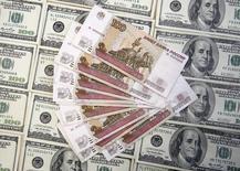 Долларовые и рублевые купюры в Сараево 9 марта 2015 года.  Рубль дешевеет при низкой активности и небольших биржевых объемах на торгах пятницы, выходного дня в США, и перед сегодняшней публикацией свежего инвестиционного рейтинга России, а также в ожидании итогов воскресного греческого референдума. REUTERS/Dado Ruvic