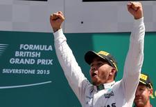 Mercedes' Lewis Hamilton celebrates his win on the podium. Reuters / Paul Childs