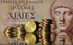 Euro coins are seen in front of a displayed of Head of Apollo on 1.000 Drachma old Greece banknote in this photo illustration taken in Zenica, Bosnia and Herzegovina, June 30, 2015. REUTERS/Dado Ruvic