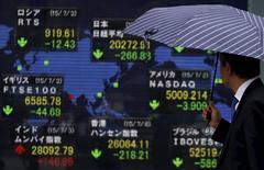 Un peatón mira un tablero electrónico que muestra los índices de mercado de varios países afuera de una agencia de la bolsa en Tokio, Japón, 6 de julio de 2015. Las bolsas de Asia cotizaban en mínimos en seis meses y el euro se debilitaba el lunes después de que una votación griega contra las medidas de austeridad puso en riesgo el futuro de Atenas en la zona euro y elevó el riesgo de una crisis en toda regla en el bloque monetario. REUTERS/Yuya Shino