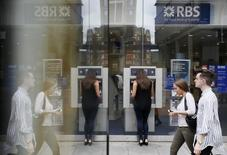 Pedestrians are reflected in the glass of an advertising board as they walk past a branch of The Royal Bank of Scotland in central London, Britain June 17, 2015. REUTERS/Stefan Wermuth
