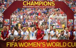 United States goalkeeper Hope Solo (1) hoists the FIFA Women's World Cup trophy as she and her teammates pose with their medals after defeating Japan in the final of the FIFA 2015 Women's World Cup at BC Place Stadium. The United States won 5-2. Mandatory Credit: Anne-Marie Sorvin-USA TODAY Sports