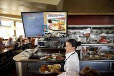 Una mesera avanza con unos pedidos en el restaurante Norms Diner en el bulevar La Cienega en Los Angeles, EEUU, mayo 20 2015. El ritmo de crecimiento en el sector de servicios de Estados Unidos aumentó en junio después de caer en mayo a un nivel mínimo en 13 meses, con una mejoría de las lecturas de actividad empresarial y nuevos pedidos, mostró un reporte de la industria publicado el lunes. REUTERS/Patrick T. Fallon