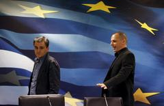 Outgoing Finance Minister Yanis Varoufakis (R) shows newly-appointed Finance Minister Euclid Tsakalotos his chair at the Finance Ministry before a handover ceremony in Athens, Greece July 6, 2015.  REUTERS/Yannis Behrakis
