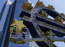 Trabalhadores desmontam a escultura que representa o euro para uma manutenção, em frente à ex-sede do Banco Central Europeu (BCE), em Frankfurt, na Alemanha, nesta segunda-feira. 06/07/2015 REUTERS/Ralph Orlowski