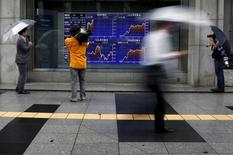 Una persona filma un tablero electrónico que muestra las tasas cambiarias entre el yen japonés, el dólar estadounidense y el euro, afuera de una agencia de la bolsa, en Tokio, Japón, 6 de julio de 2015. La mayoría de las bolsas de Asia caía el martes, lastradas por un nuevo desplome en los mercados bursátiles chinos, lo que agitaba los nervios de los inversores ya tensos por la incertidumbre sobre el futuro de Grecia y de la unión monetaria europea. REUTERS/Yuya Shino