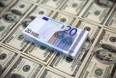 Купюры валют доллар США и евро в Сараево 9 марта 2015 года. Курс евро снижается, а иена дорожает, так как инвесторы предпочитают низкорискованные активы на фоне падения китайского фондового рынка. REUTERS/Dado Ruvic