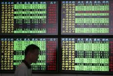 En la imagen de archivo, un inversor camina frente a monitores con información financiera en una agencia de la bolsa en Shanghái, China, el 3 de julio de 2015. El Gobierno de China planea gastar 250.000 millones de yuanes (unos 40.300 millones de dólares) para estimular el crecimiento en las áreas de la economía que más necesitan apoyo, anunció el miércoles el Gabinete de China. REUTERS/Aly Song